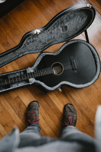Man looking down at his guitar on the floor
